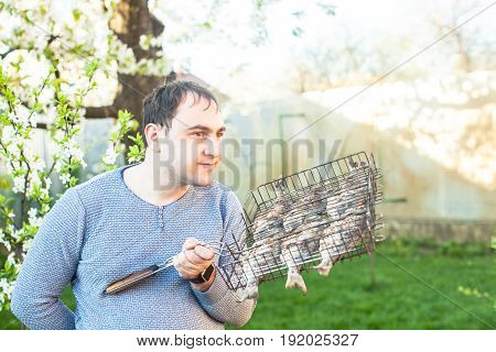 Man holding grilled fish in a steel grid.