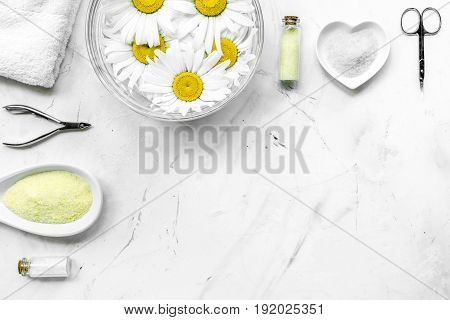 Spa composition on white desk with salt, chamomile, towel and manicure set copyspase top view.