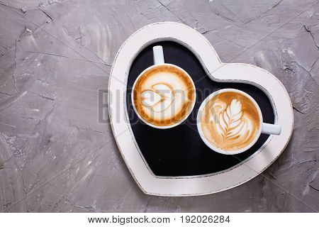 Latte art in two cups of cappuccino on the heart shape tray. Happy morning Valentine day couple