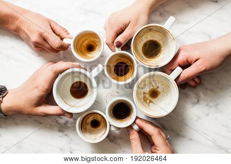 Top view hands holding empty and dirty cups of coffee afterparty