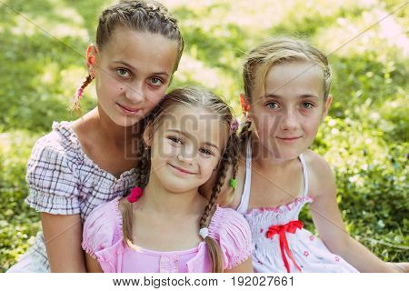 Three girls sit on the grass and smile