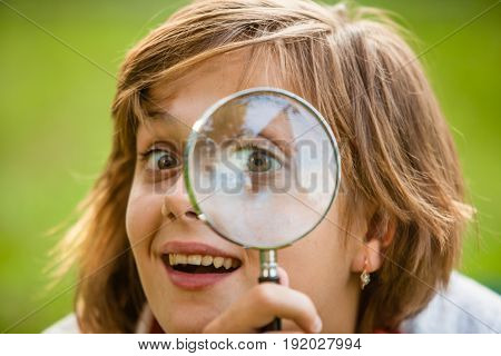 Teen uses magnifying glass to discover nature