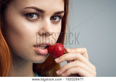 Woman with strawberry, sweet strawberry, woman eating strawberries on gray background portrait.
