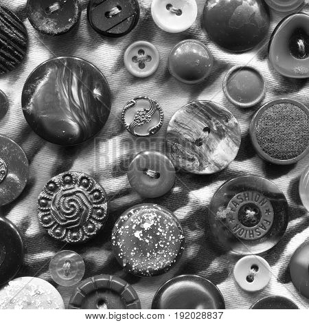 Abstract black and white background of buttons. Buttons of the circle shape of variation textures randomly arranged in the form of a pattern on a fabric