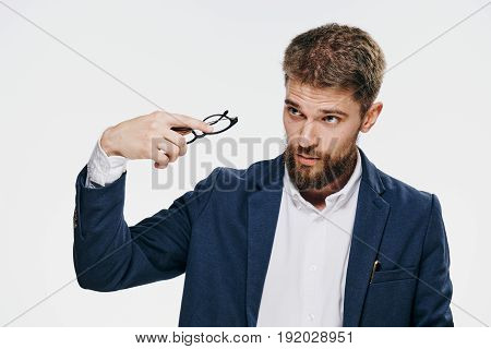 Businessman taking off glasses, businessman looking away, businessman on light background.