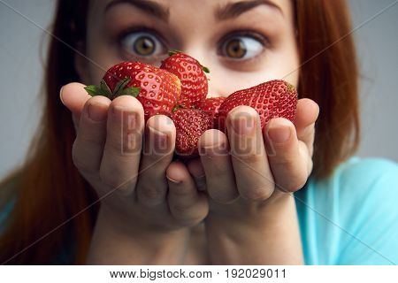 A handful of strawberries, a lot of strawberries in the hands of a woman, a woman with strawberries.