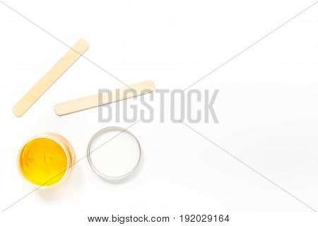 Wax and stick for depilation on white background top view copyspace.