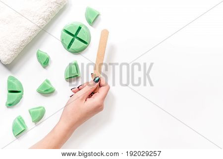 Woman hand takes wax for depilation by stick. Set for depilation on white background top view.
