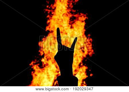 Silhouette of Rock and Roll hand sign against the fire background.