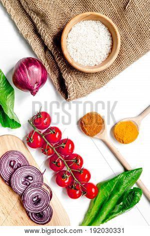 homemade paella ingredients composition with rice, tomato, onion on white kitchen table background top view