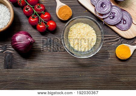 rise, spices and vegetables for paella on wooden kitchen desk background top view space for text