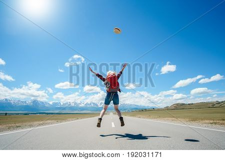 Full Length Rear View Of Woman Jumping While On Road Against Sky.