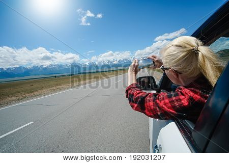 Woman Photographed From The Car Window A Smartphone.