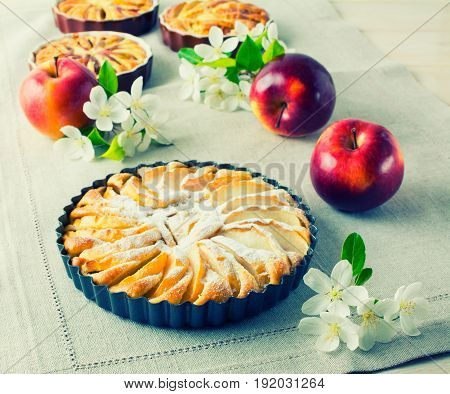 Sweet apple pie with spring flowers and ripe fruits toned