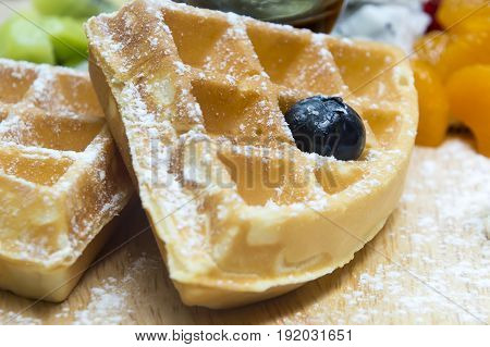 Waffles with berriesfruit and ice-cream in wood plate on table.