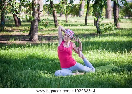 Young Woman Doing Yoga And Gymnastics In The Park.