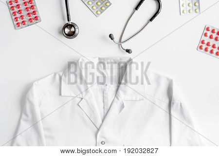 Modern medicine workplace with overall, meds and stethoscope on white table background flat lay space for text