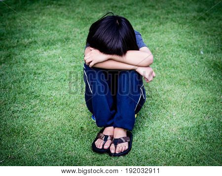 little boy unhappy sad and sitting alone on the grass field