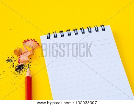 Sharpening a red pencil sharpener and the note book On yellow background.