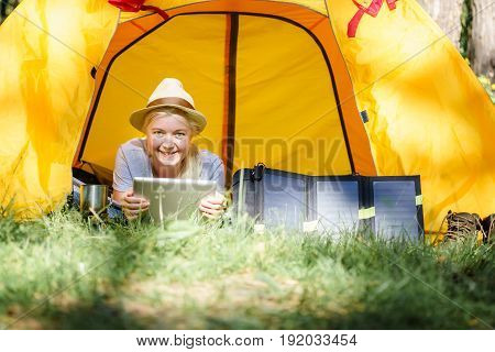 Woman Using Digital Tablet In Tent In The Woods.
