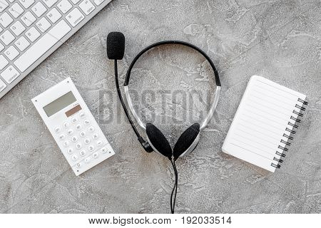 contact us for company feed back with headset and notebook on stone desk background top view mock-up
