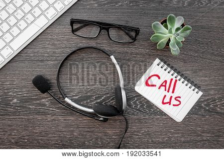 contact us for company feed back with headset and notebook on wooden desk background top view