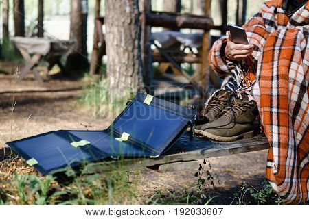 Woman Using Smartphone In The Woods.  Charges Using Solar Panels.