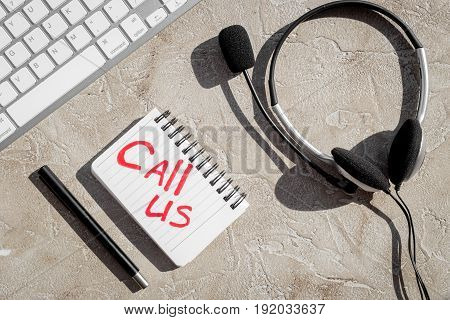 customer support service desktop with contact us copy on stone background top view