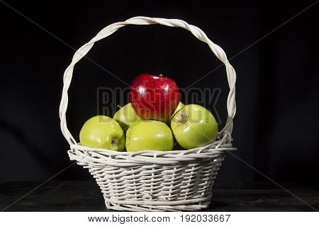 Ripe apples in a wicker basket on a black background