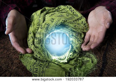 Fortune tellers hands or psychic over a glowing crystal ball. The occult object has a mysterious magical light. The image depicts pagan spirituality or superstition and witchcraft. poster