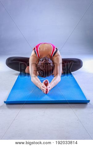 Close up of young woman practicing yoga at home interior background sitting in head to knee forward bend exercise