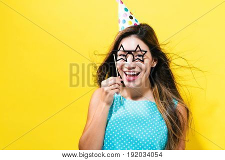 Young woman with party hat with paper party glasses on a yellow background