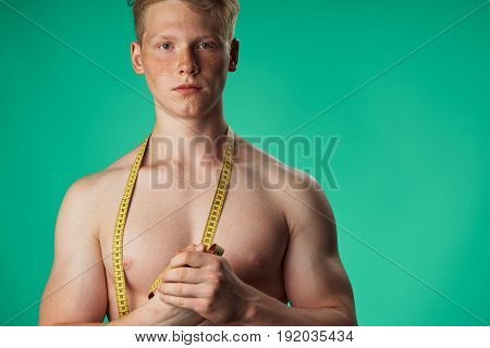 Mans sporty appearance, man with a measuring tape on a green background.