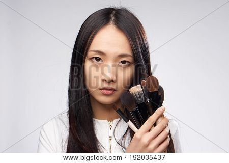 Woman with make-up brushes, make-up brushes, woman on a light background.