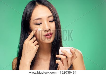 Woman applying cream on face, woman with cream, woman on green background.