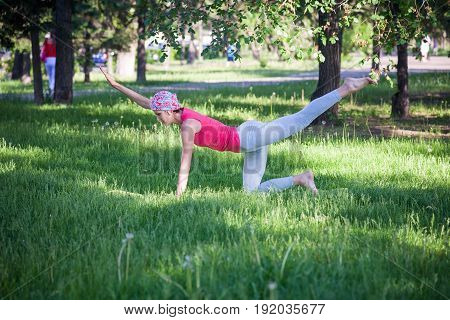 flexible young woman practicing yoga and gymnastics in the Park. Yoga in the Park, outdoors , women's health, Yoga woman. The concept of healthy lifestyle and recreation