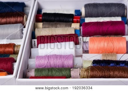 Various Multicolored Used Sewing Threads In A Box, Stacked In A Pile