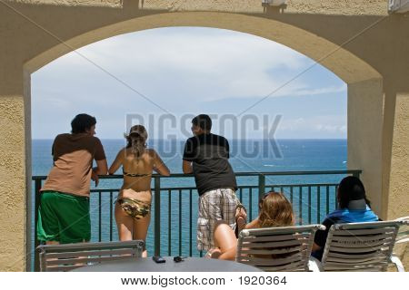 Young People Gaze At Ocean Under Arch
