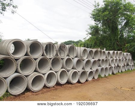 heap of concrete drainage pipes stacked on construction site with diminishing perspective