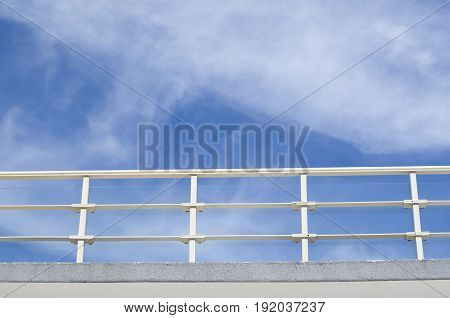 Balcony with white parapet of the blue cloudy sky