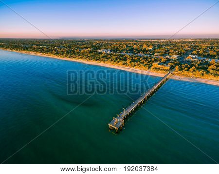 Aerial View Of Long Wooden Pier And Beautiful Coastline At Vivid Sunset.