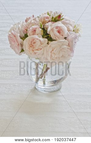 Arrangement of wild pink roses in vase on white tablecloth