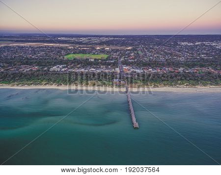 Aerial View Of Seaford Suburb In Melbourne And Long Wooden Pier At Dusk.