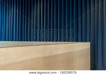 Wooden Office Cubicle Wall Over Blue Curtains