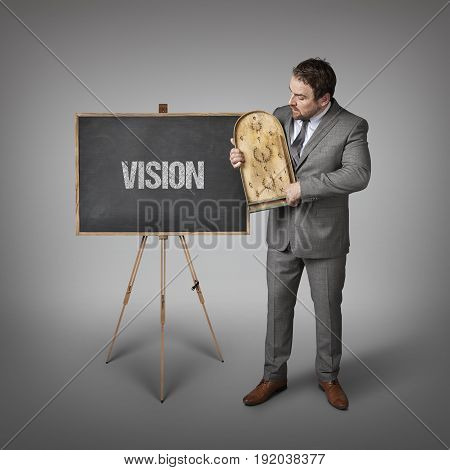 Vision text on blackboard with businessman and abacus