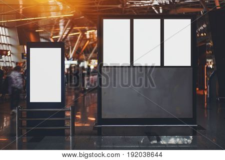 Blank four electronic departures and arrival informational billboards with clean space for publicity content or messages narrow advertising mock-up placeholders in interior in airport terminal hall