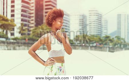 Young beautiful pensive Brazilian girl staying on beach in Rio de Janeiro on warm sunny with embankment and tall residential houses in blurred background with copy space zone for your logo or message