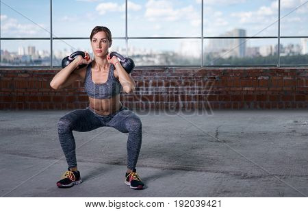 Woman athlete squat with weights. Copy space. Fitness concept
