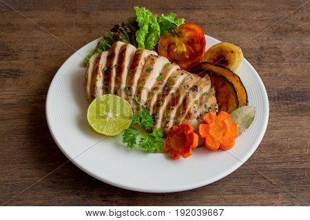 Sliced chicken breast barbecue on white plate served with grilled vegetable. Delicious chicken breast steak and salad for dinner. Homemade chicken breast barbecue on wood table for background. Chicken barbecue or pork steak.
