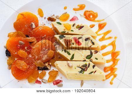 Dried apricots, halva, marmalade, raisins, walnuts, dried melon and sunflower seeds. A plate of oriental sweets